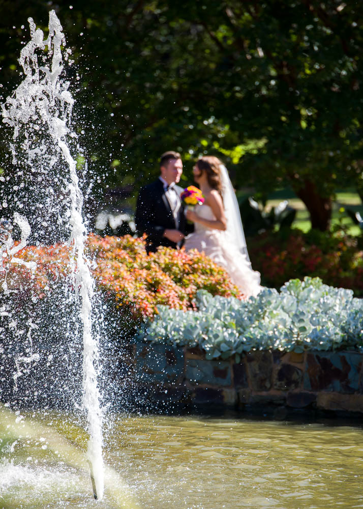 Bride and groom in background of fountain, Fitzroy Gardens Treasury Gardens, Place
