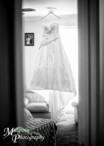 Bride Emily's dress hanging in the bedroom