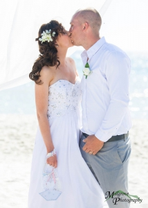 Bride and groom kissing at the beach wedding