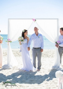 Unique bride and groom image, very smiling and happy, at the beach in Melbourne