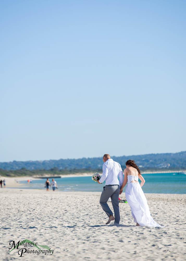 Bride Rachel and Groom Phill walking on the beach