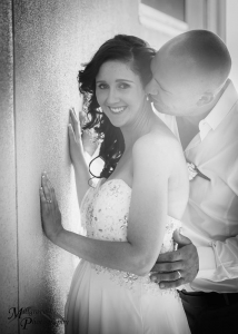 Groom whispering to bride as she's smiling