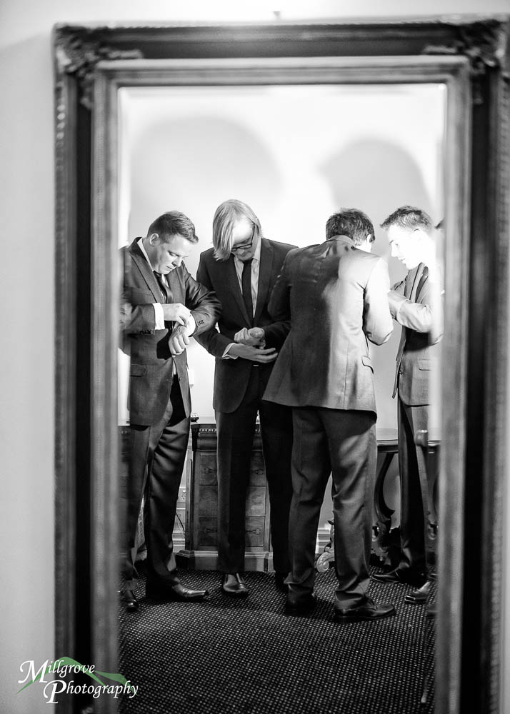 Groomsmen preparing for a wedding, reflected in a mirror