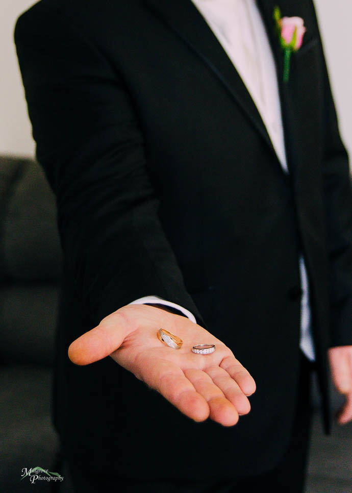 Groom holding rings on hands