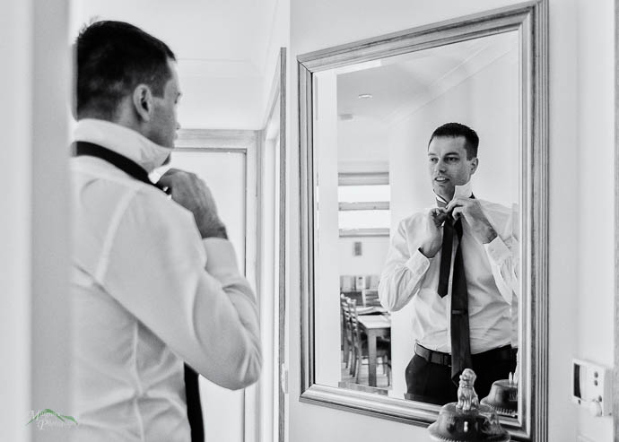 Groom doing up his tie in the mirror