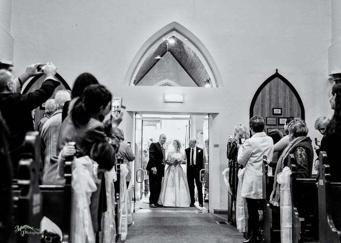 Bride and companions walking down aisle