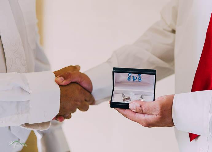 Groom handing cufflinks to a groomsman