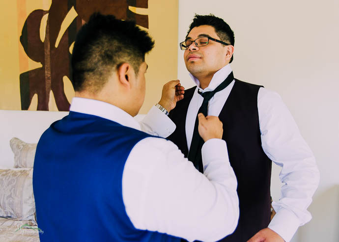 Groomaman helping groom do up his tie