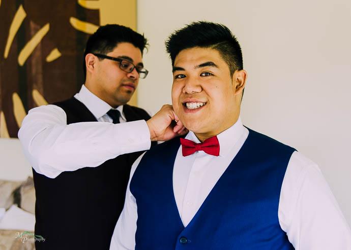 Groom helping groomsman do up his tie