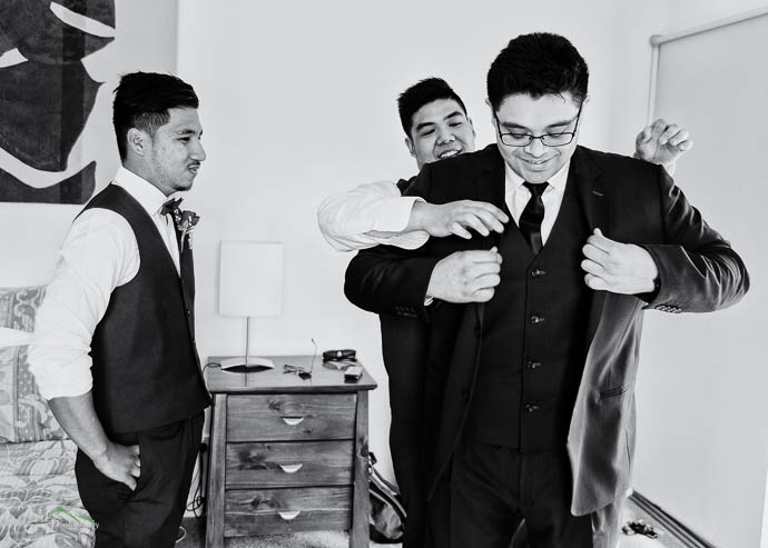 Black and white, groomsman helping groom with his jacket