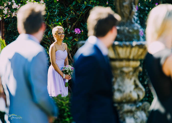 Bridesmaid walking down the aisle at a Roselyn Court wedding in