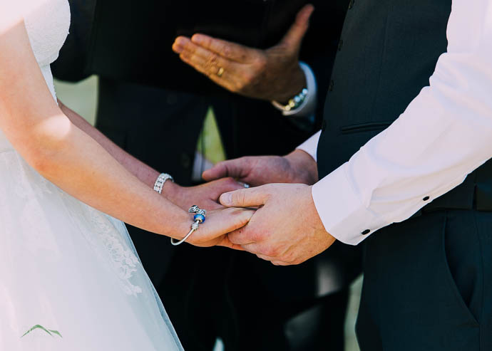 Bride and groom holding hands in close up