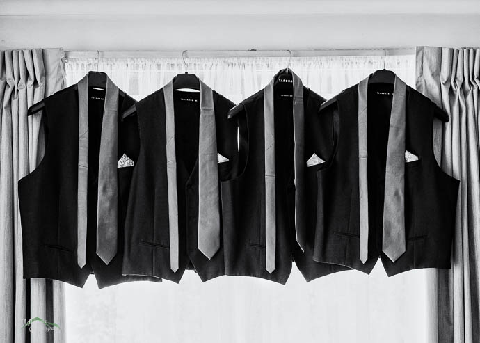 Four waistcoats, vests, and ties hanging in a window