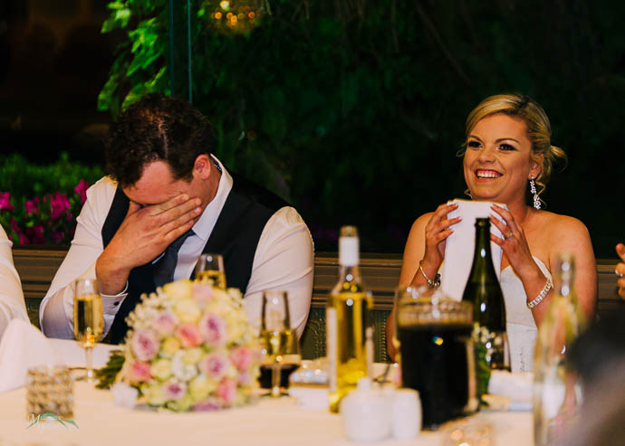 The bride and groom laughing during speeches