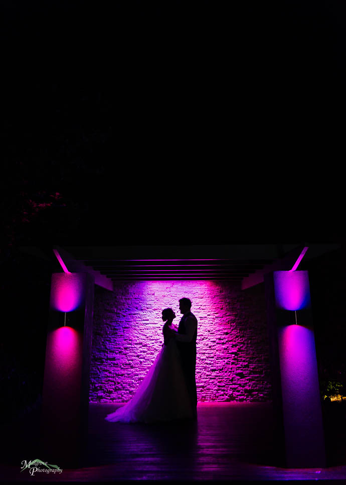 Bride and groom silhouetted against a pink wall at Roselyn Court