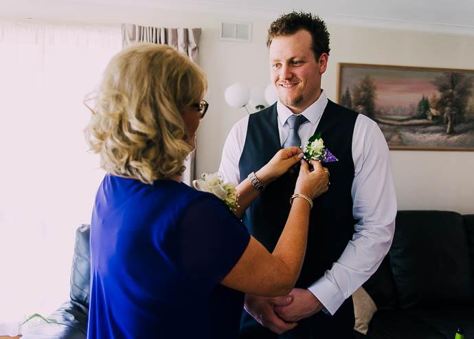Mum pinning flowers on groom