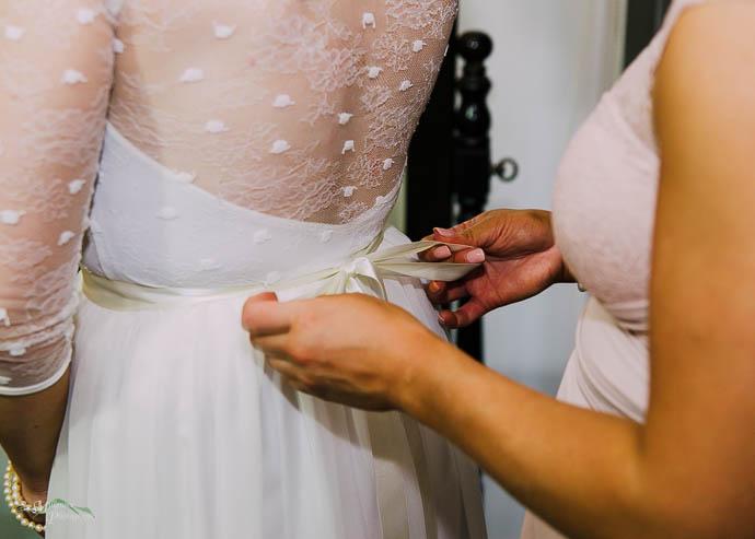 Bridesmaid adjusting ribbon on bride's dress