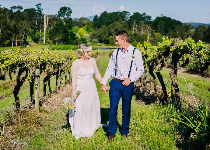 Bride and groom walking amongst the vines at a vineyard wedding