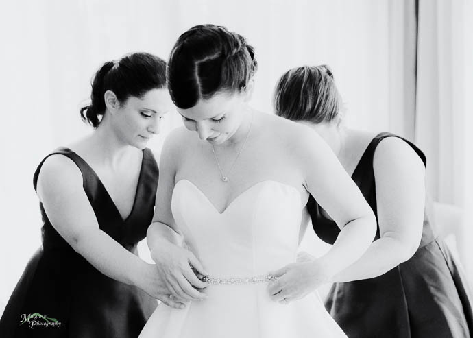 Bride putting on her earrings in the bridal suite at Lake House,