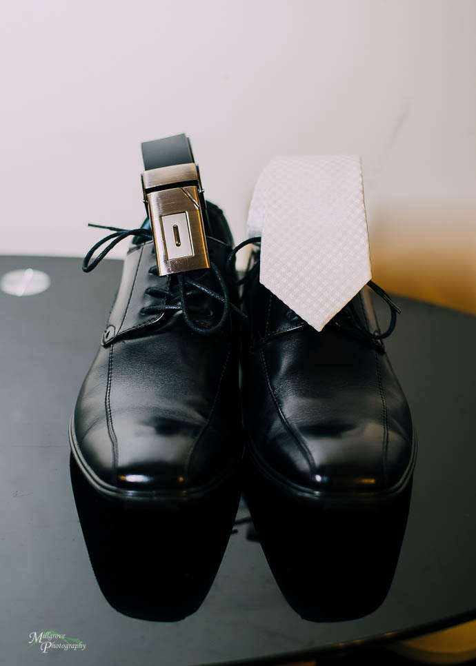 Groom's shoes with his tie and belt placed on top
