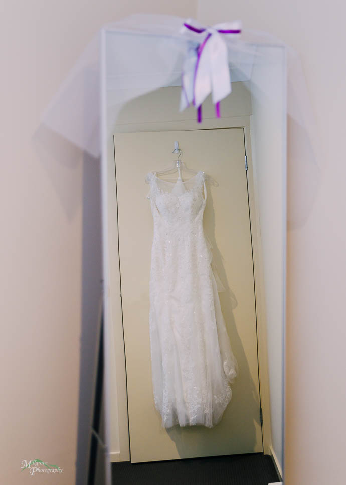 Bride's dress hanging against a door