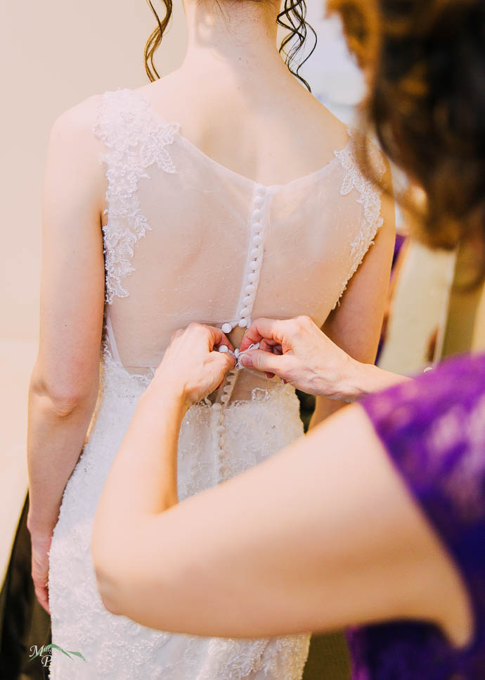 Mum helping Bride with her dress