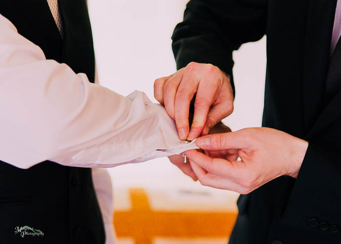 Groom getting help from Groomsmen to put on his cufflinks