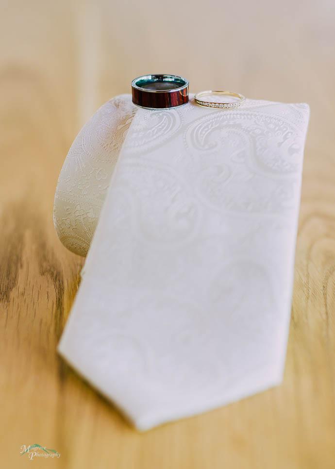Wedding rings balanced on a white tie