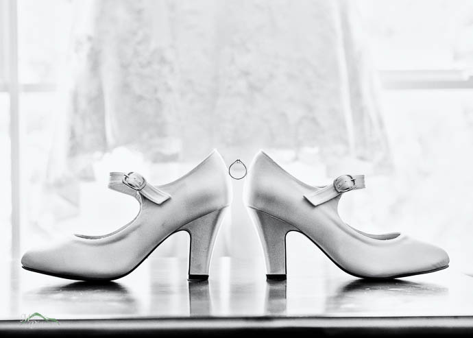 Bride's shoes with ring balancing in between, black and white