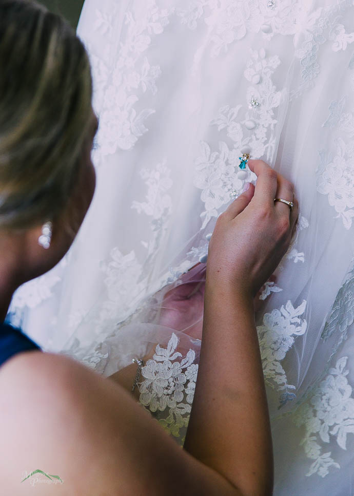 Bridesmaid pinning something onto Bride's dress