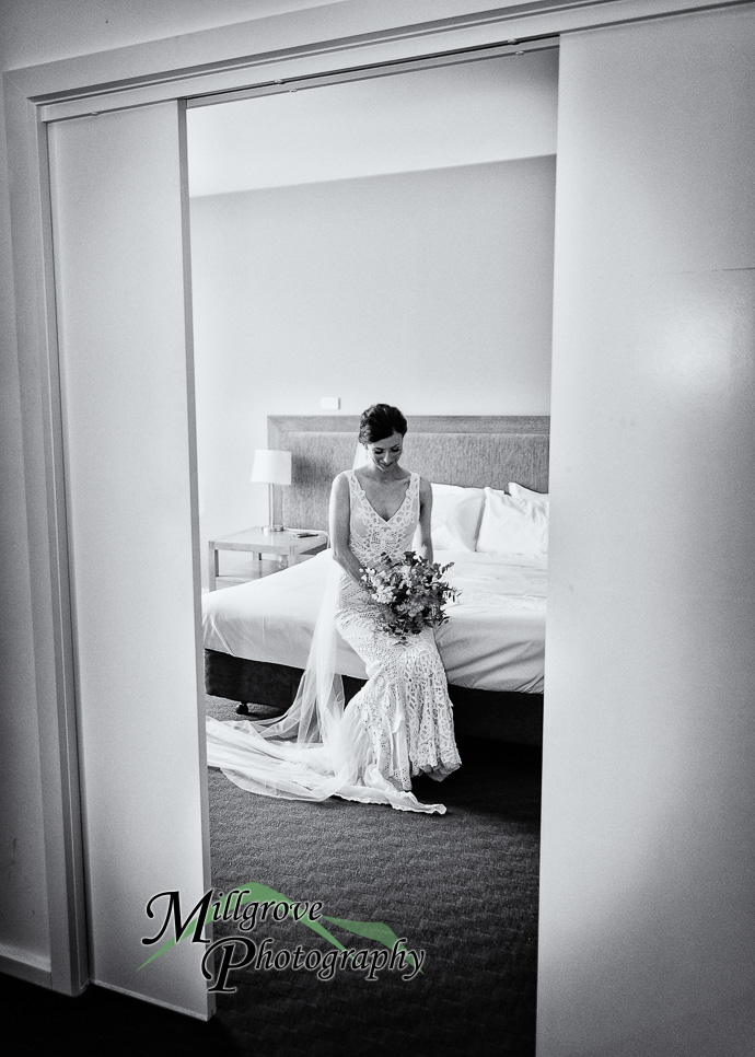 A bride sitting on a bed in black and white