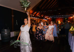 Bride throwing her bouquet of flowers to her waiting friends and bridesmaids, captured by a candid wedding photographer