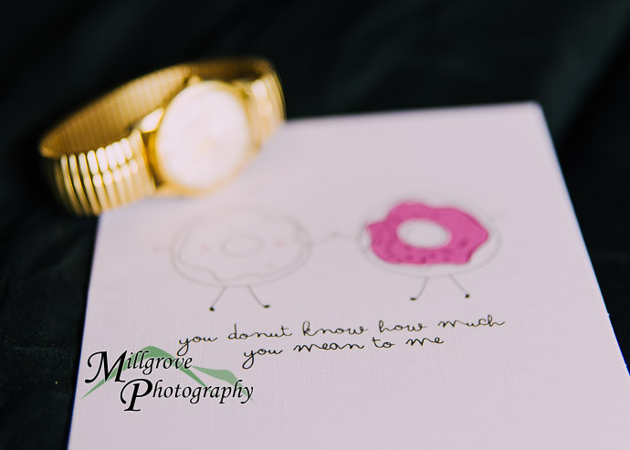 A gold watch on a wedding invitation