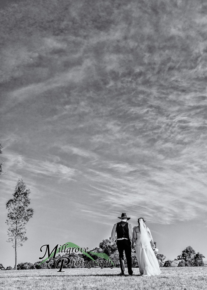 A bride and groom posing for photos outside on a hill
