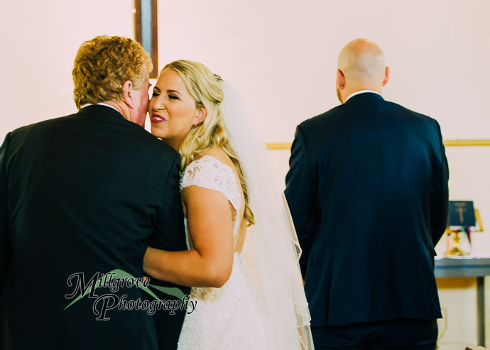 A woman kissing her father at a wedding
