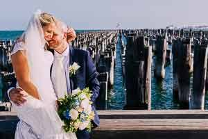 Bride and groom sharing a cute moment in front of the pylons at Station Pier, Port Melbourne Wedding