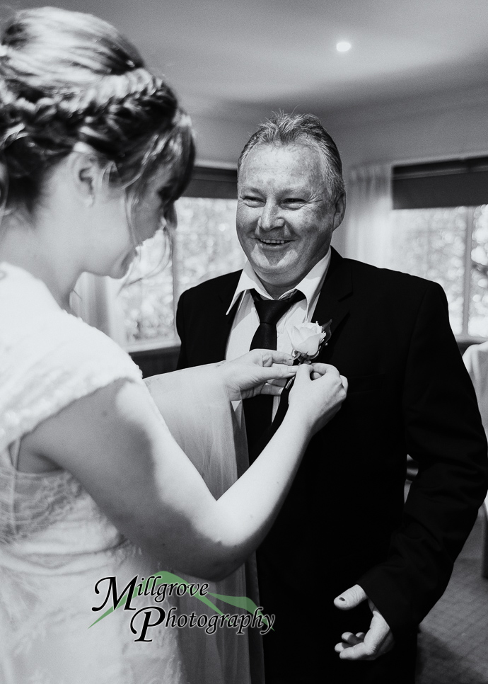 Bride pinning a flower to her father's lapel