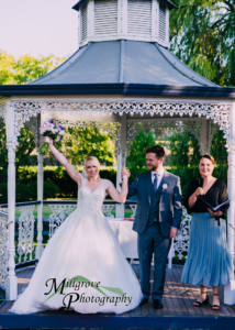 Bride and Groom celebrating after being declared husband and wife, captured by a candid wedding photographer at an outdoor wedding photography Melbourne ceremony