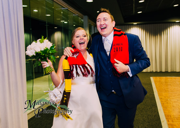 bride and groom with footy scarves