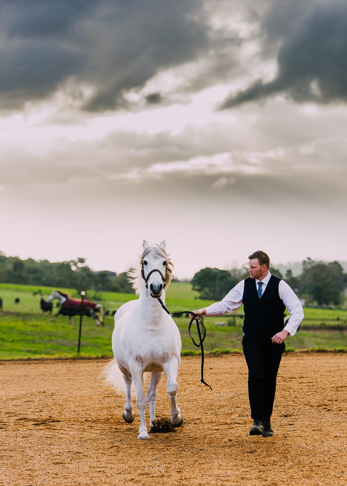 Groom running with a horse in his wedding clothes.