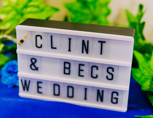 "A signboard that reads ""Clint and Bec's wedding"""