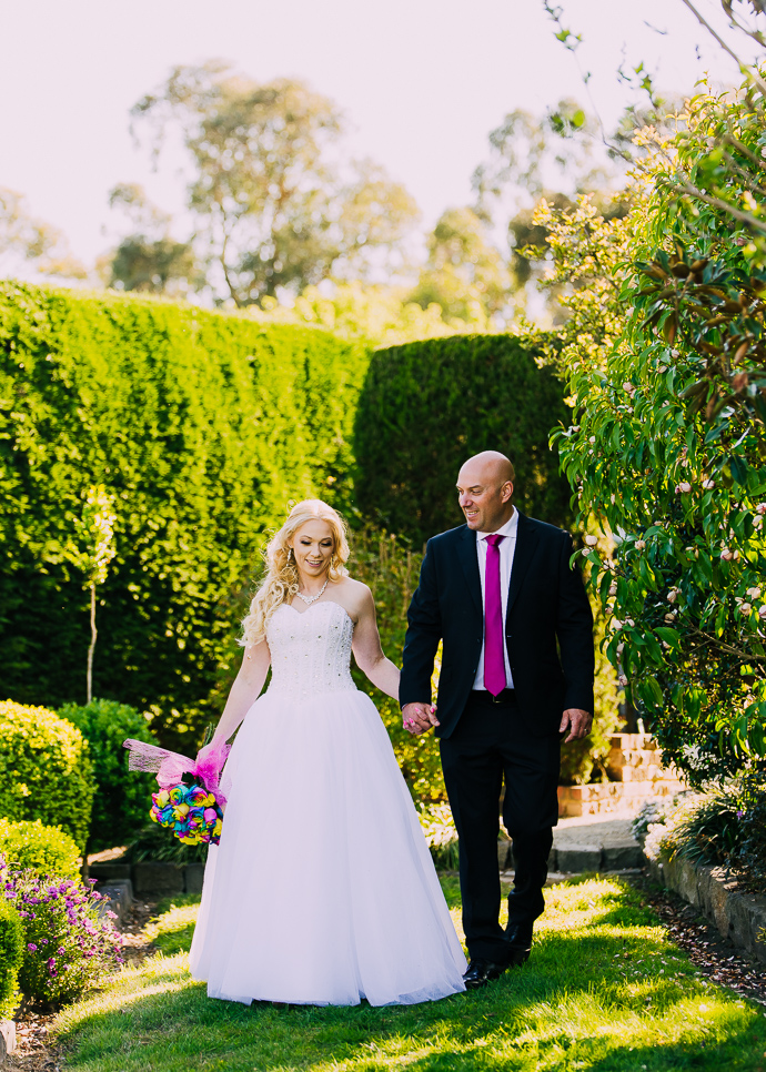A bride and groom posing for wedding photos in a garden