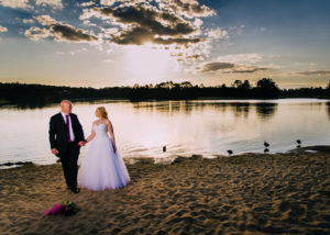 A couple standing by a lake at sunset, pre Coldstream Brewery reception