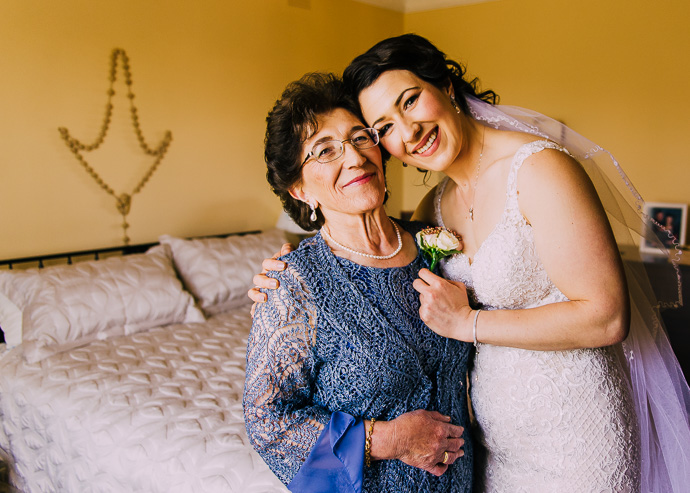 A bride pinning a flowers on her mother's dress