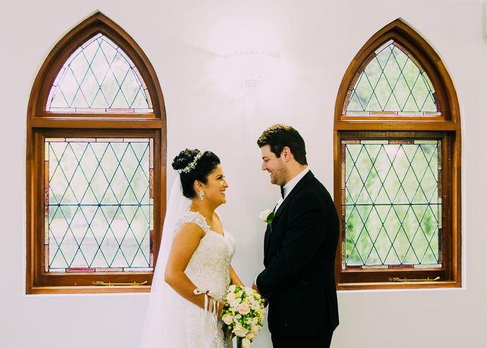 A bride and groom by a chapel window