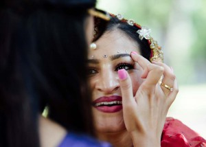 Bride having eye makeup touched up before wedding