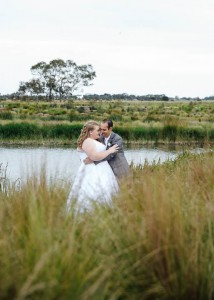 Bride and groom with grass in the foreground