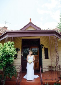 Bride standing outside house