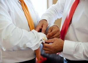 Groomsman helping with cufflinks