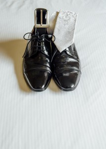 shoes, belt and tie on bed